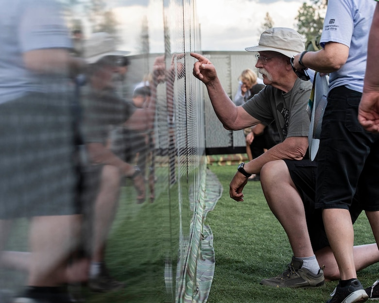 """Visitors of """"The Moving Wall,"""" a half-size replica of the Vietnam Memorial that stands in Washington D.C., search for names of loved ones, friends, and comrades lost on the Vietnam War following the opening ceremony of the wall June 13, 2019 in Medical Lake, Wash. Visitors can view the display 24 hours a day at the 200 block of South Prentis St. in Medical Lake. (U.S. Air National Guard photo by Staff Sgt. Rose M. Lust/Released)"""
