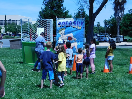 Lanora Cox, 60th Force Support Squadron librarian for the Mitchell Memorial Library, falls into a dunk tank during the Summer Reading Program kick-off event June 10, 2019, at Travis Air Force Base, California. The program, now in its second decade, promotes reading and learning across all ages. (U.S. Navy photo by Petty Officer 3rd Class Malcolm Kelley)