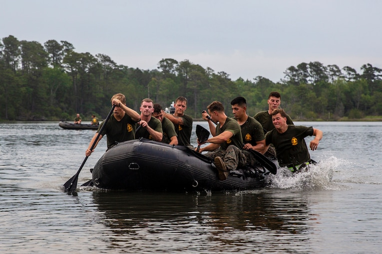 A group of Marines row a craft on water.
