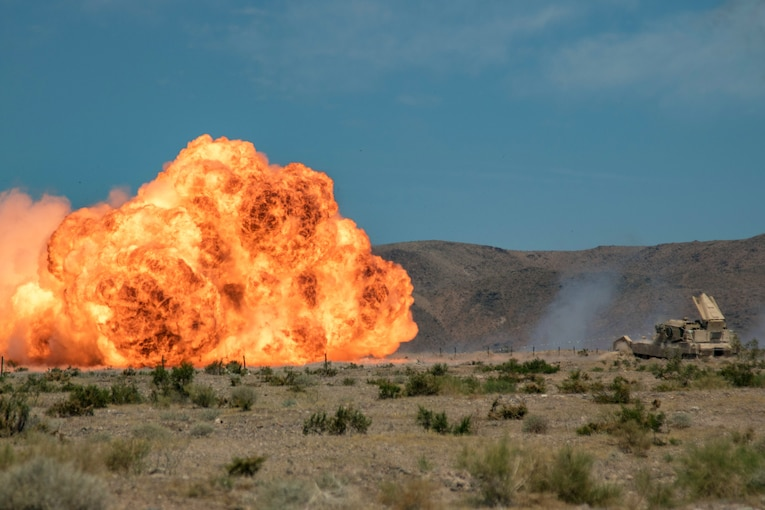 Soldiers in a tank set off a ball of fire.