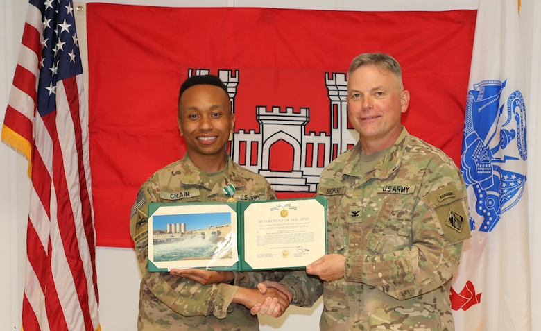 "Capt. Sean Crain (left) is presented with an Army Commendation Medal by U.S. Army Corps of Engineers Mosul Dam Task Force Commander Col. Philip Secrist during a ceremony held in Mosul, Iraq on June 14, 2019. Crain authoring more than 20 project reports in order to keep various high level stakeholders including the Government of Iraq and the U.S. Embassy in Iraq informed. Mosul Dam is a well-designed and well-constructed dam that is unique in that it requires continuous maintenance grouting operations due to the geology under the dam. USACE arrived at Mosul Dam in September 2016 to serve as ""the Engineer"" providing construction management, quality assurance, engineering and technical oversight and project management services in connection with a contract between Iraq and an Italian company for maintenance grouting and rehabilitation of the bottom outlet of the Mosul Dam."