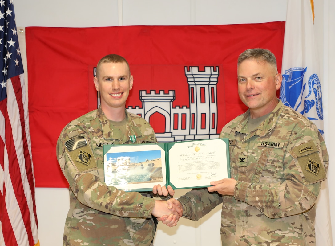Capt. William Mengon (left) is presented with an Army Commendation Medal by Mosul Dam Task Force Commander Col. Phillip Secrist during a ceremony held in Mosul, Iraq on June 14, 2019. Mengon was assigned to MDTF where he advised the Iraqi Ministry of Water Resources on warehouse operations.