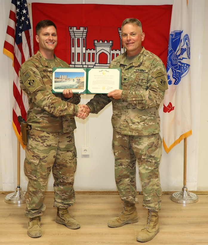 """Capt. Michael Reilly (left) is presented with an Army Commendation Medal by U.S. Army Corps of Engineers Mosul Dam Task Force Commander Col. Philip Secrist during a ceremony held in Mosul, Iraq on June 14, 2019. Mengon was assigned to MDTF where he advised the Iraqi Ministry of Water Resources on warehouse operations. Mosul Dam is a well-designed and well-constructed dam that is unique in that it requires continuous maintenance grouting operations due to the geology under the dam. USACE arrived at Mosul Dam in September 2016 to serve as """"the Engineer"""" providing construction management, quality assurance, engineering and technical oversight and project management services in connection with a contract between Iraq and an Italian company for maintenance grouting and rehabilitation of the bottom outlet of the Mosul Dam."""