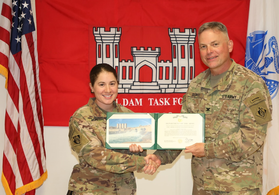 """Capt. Laura Winn (left) is presented with an Army Commendation Medal by U.S. Army Corps of Engineers Mosul Dam Task Force Commander Col. Philip Secrist during a ceremony held in Mosul, Iraq on June 14, 2019. Winn served as a battle captain, requesting and monitoring air movements for the entire task force, maintaining accountability and force-protection procedures.Mosul Dam is a well-designed and well-constructed dam that is unique in that it requires continuous maintenance grouting operations due to the geology under the dam. USACE arrived at Mosul Dam in September 2016 to serve as """"the Engineer"""" providing construction management, quality assurance, engineering and technical oversight and project management services in connection with a contract between Iraq and an Italian company for maintenance grouting and rehabilitation of the bottom outlet of the Mosul Dam."""