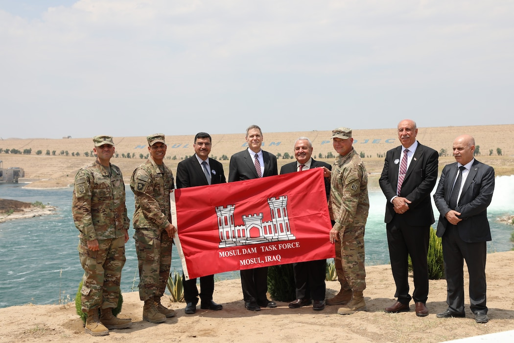 Members of the U.S. Army Corps of Engineers, the U.S. Ambassador to Iraq, and members of the Government of Iraq celebrate the completion of the Mosul Dam Task Force mission in Iraq by holding up the MDTF Mission Flag on the banks of the Tigris River in front of the dam. Pictured left to right are: U.S. Army Corps of Engineers Transatlantic Division Command Sergeant Major Randolph Delapena, TAD Commander Col. Mark Quander, Iraq Minister of Water Resources Director General Mahdi Rashid, U.S. Ambassador to Iraq Matthew H. Tueller, Iraq Minister of Water Resources Jamal al-Adili, Mosul Dam Task Force Commander Col. Philip Secrist, Mosul Dam Project Manager Riyadh Ali, and Iraq Director General of Planning and Follow-up Jamal Mohsin. The dignitaries were visiting the MDTF on June 15, 2019, for a ceremony commemorating the completion the Mosul Dam Project, which started in 2016 as a joint project among the Iraq Ministry of Water Resources, the U.S. Army Corps of Engineers, and Italian Company Trevi S.p.A. in an effort to stabilize the infrastructure of the Mosul Dam. The Dam is the largest in Iraq and the fourth largest in the Middle East. It supplies water, hydropower, irrigation and flood control to the region.