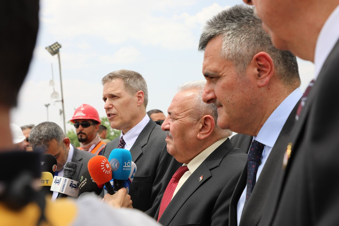 """The U.S. Ambassador to Iraq, Matthew Tueller, speaks to media following a ceremony June 15, 2019, at the Mosul Dam in Iraq. Also picture are Iraq Minister of Water Resources Jamal Abbas al-Adili, and Italian Ambassador to Iraq Bruno Pasquino. The ceremony was held to commemorate the completion of USACE's work supporting the Mosul Dam Project. The Mosul Dam Project started in 2016 as a joint project among the Iraq Ministry of Water Resources, USACE, and Italian Company Trevi S.p.A. in an effort to stabilize the infrastructure of the Mosul Dam. The dam, which is the largest in Iraq, and the fourth largest in the Middle East, supplies water, hydropower, irrigation and flood control to the region. USACE's Mosul Dam Task Force acted as """"The Engineer"""" for the joint endeavor."""