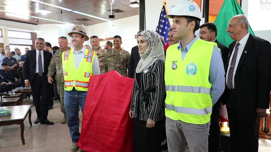 Workers from the U.S. Army Corps of Engineers, the Iraqi Ministry of Water Resources and Italian Company Trevi S.p.A. stand ready to unveil a new plaque that will hang at Mosul Dam, commemorating the 3-year partnership between the three countries of Iraq, the U.S. and Italy. The plaque was unveiled during a ceremony on June 15, 2019, at the Mosul Dam in Iraq. The Mosul Dam Project started in 2016 as a joint project among the Iraq Ministry of Water Resources, the U.S. Army Corps of Engineers, and Trevi in an effort to stabilize and repair the infrastructure of Mosul Dam. The dam, which is the largest in Iraq, and the fourth largest in the Middle East, supplies water, hydropower, irrigation and flood control to the region.