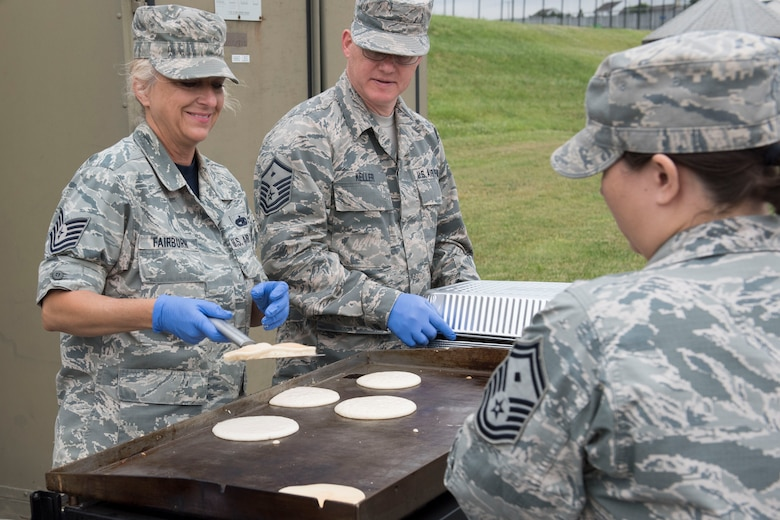 Tech. Sgt. Shannon Fairburn and Master Sgt. James Keller, members of the 167th Airlift Wing, serve pancakes outside of building 309 at the 167th Airlift Wing, June 6, 2019. The pancake breakfast was sponsored and planned by the First Sergeant Council. Approximately 300 Airmen enjoyed the pancakes and about $200 was raised in donations that the council plans to use towards different sponsorships. (U.S. Air National Guard photo by Tech. Sgt. Michael Dickson)
