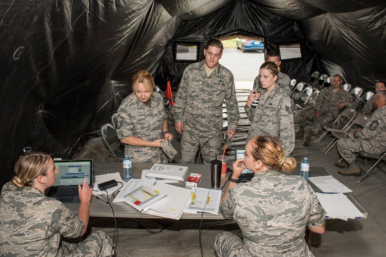 Airmen check in for their physical health assessment in a tent set up outside of the medical clinic as part of a new process tested by the 167th Medical Group, June 7, 2019. Check-in was moved outside to free space inside the building allowing more space to be used for exams and lab space. (U.S. Air National Guard photo by Tech. Sgt. Michael Dickson)