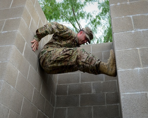 An Air Force recruiter with the 330th Recruiting Squadron practices climbing a wall following instruction from survival, evasion, resistance and escape cadre members from 66th Training Squadron, Det. 3, at Joint Base San Antonio-Lackland June 3. Survival, Evasion, Resistance and Escape cadre are responsible for both the four-day Evasion and Conduct After Capture Course and the 15-day SERE Specialist Training Orientation Course at JBSA-Lackland. ECAC was the first stop for recruiters from the 330th RCS who travelled from across the United States to attend this biannual squadron training intended to immerse recruiters into SERE training in order for them to be better able to recruit Air Force SERE candidates.