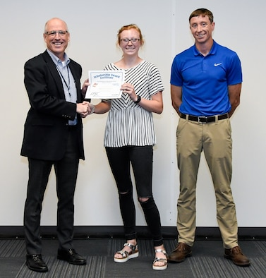Dr. Rich Tighe, left, general manager of the Test Operations and Sustainment contractor at Arnold Air Force Base, presents a certificate to Kayden Fletcher recognizing her as one of the 2019 Bechtel Global Scholars during a meeting June 7 at Arnold. Also pictured is Kayden's father Jeremy Fletcher, a Propulsion Wind Tunnel controls engineer at Arnold. Kayden will receive a $3,000 scholarship funded by the Bechtel Group Foundation for her first year of study at an accredited institution. (U.S. Air Force photo by Jill Pickett) (This image has been altered by obscuring a badge for security purposes.)