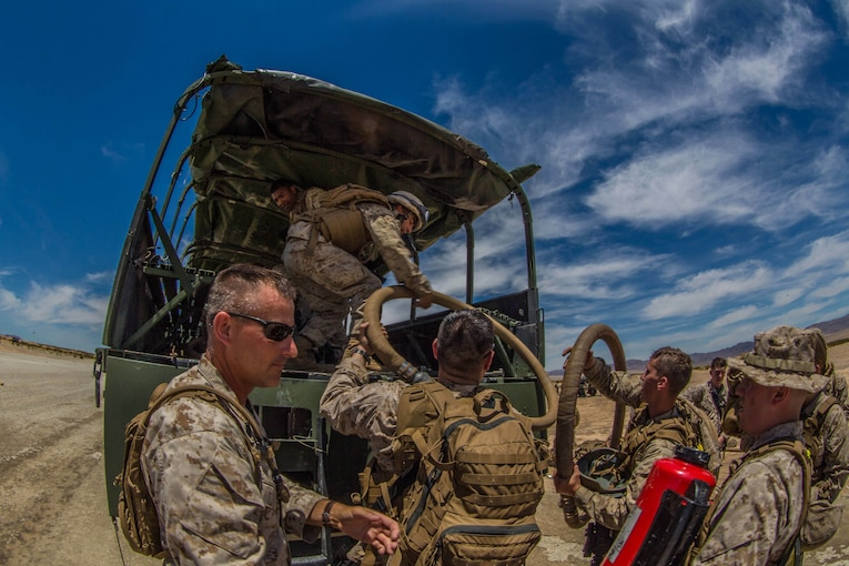 Marines load equipment into a truck.