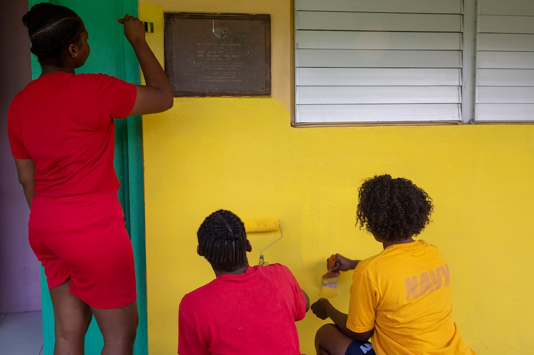 A sailor and two students paint a building bright yellow.