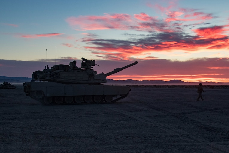 A tank sits outside as dawn breaks with scattered red clouds overhead.