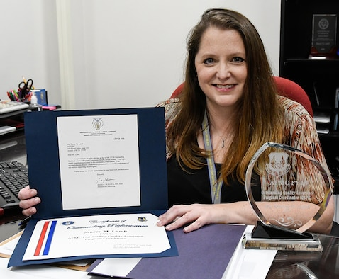 Stacey Lamb, AEDC Quality Assurance Program Coordinator and Small Business Specialist at Arnold Air Force Base, displays the award and certificate she received for being named the Air Force Materiel Command Outstanding Quality Assurance Program Coordinator for fiscal year 2018. (U.S. Air Force photo by Jill Pickett) (This image was altered by obscuring items for security purposes.)