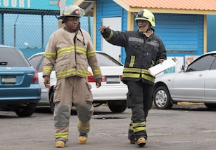 Members of the Saint Vincent and the Grenadines fire department put out a simulated fire upon arrival during phase II of Tradewinds 2019.