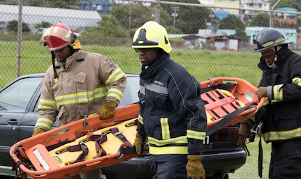 Three firemen with the Saint Vincent and the Grenadines fire department prepare to evacuate wounded in simulated training exercise during phase II of Tradewinds 2019
