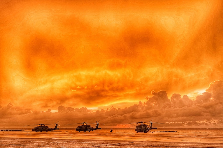 A trio of MH-60R Seahawk helicopters line a beach at sunrise.