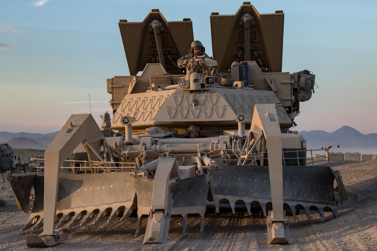 A soldier sits at the top of a huge military vehicle in the desert.