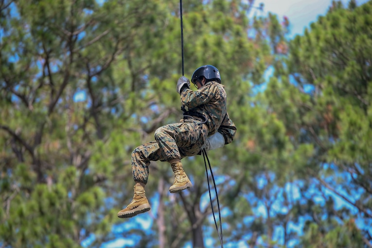 A Marine Corps recruit rappels down from a tower.