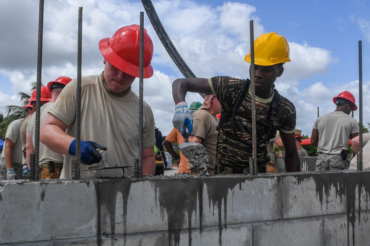 An airman and a Guyanese service member fill holes use pavers to fill holes in a concrete wall.