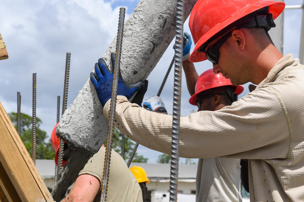 An airman wearing a hard hat pours concrete at a construction site.