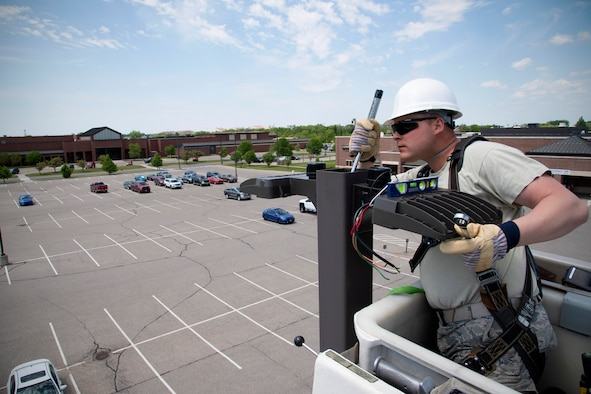 Airman 1st Class David Peranich, 319th Civil Engineer Squadron electrical systems journeyman, installs new streetlights in the commissary parking lot June 12, 2019, on Grand Forks Air Force Base, North Dakota. Peranich and other electrical systems airmen began replacing all base streetlights with brighter, more energy-efficient LED bulbs as soon as weather allowed, and are scheduled to complete their project at the end of summer. (U.S. Air Force photo by Senior Airman Elora J. Martinez)