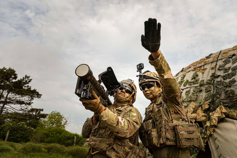 On soldier holds a missile over his shoulder while another soldier points in the distance.
