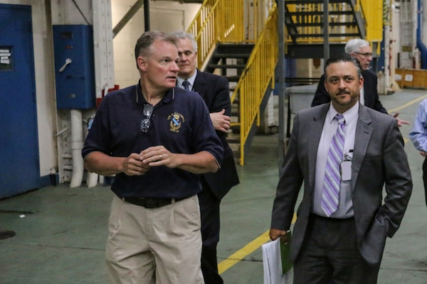 190529-N-LT766-0004 PHILADELPHIA (May 29, 2019) Andy Carirns, left, leads Steven Lagana, right, NAVSEA PMS 555 Shipyard Infrastructure Optimization Program (SIOP) on a tour of the Naval Surface Warfare Center Philadelphia Division (NSWCPD) campus. During the visit Lagana saw many test sites and labs including the Advanced Data Acquisition, Prototype Technology and Virtual Environments (ADAPTVE) lab. (U.S. Navy Photo by Mass Communication Specialist 1st Class John Banfield/Released) (This photo has been altered for security purposes by blurring out identification badges.)