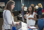 Janice Taylor, a representative from the Defense Finance & Accounting Service speaks with a potential candidate Sept. 19, 2018, during the Joint Base San Antonio-Fort Sam Houston, Texas, Department of Defense Hiring Heroes Career Fair. Army Emergency Relief recently announced a new program that would reimburse spouses up to $2,500 for relicensing expenses, making it easier for them to continue their careers when they move to another state.