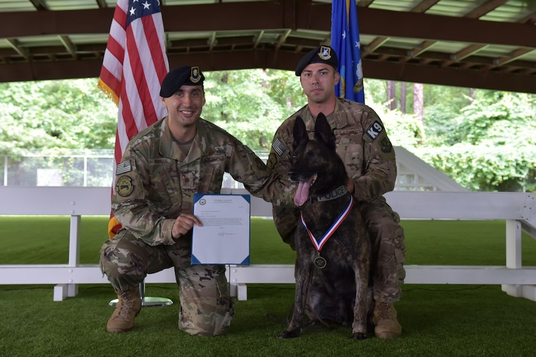 Maj. John-Paul Adrian, 4th Security Forces Squadron commander, left, and Tech. Sgt. Sergio Hernandez, 4th SFS kennel master, present Military Working Dog Ronni P835 with a 4th SFS MWD medal during Ronni's retirement ceremony on June 11, 2019 at Seymour Johnson Air Force Base, North Carolina.