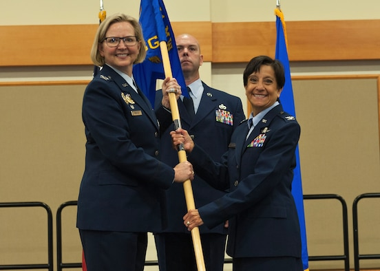 Col. Lisa Martinez, right, accepts command of the 341st Mission Support Group from Col. Jennifer Reeves, 341st Missile Wing commander during an assumption of command ceremony June 17, 2019, at Malmstrom Air Force Base, Mont. Guidon bearer Chief Master Sgt. Lance Blocher, 341st MSG group superintendent, looks on. (U.S. Air Force photo by John Turner)
