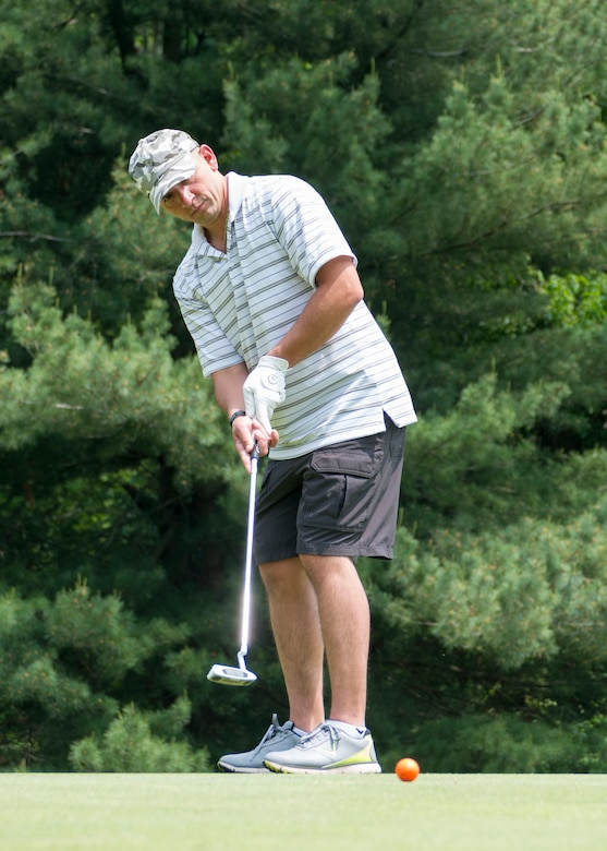Staff Sgt. David DuMouchel, of the 103rd Civil Engineer Squadron, East Granby, Connecticut, swings his golf club June 1, 2019 at the Bogies for the Brave's golf tournament at the Hunter Golf Club in Meriden, CT. DuMouchel putted the ball into the 11th hole. The tournament was hosted by the non-profit organization Bogies for the Brave. (U.S. Air National Guard photo by Airman 1st Class Chanhda Ly)