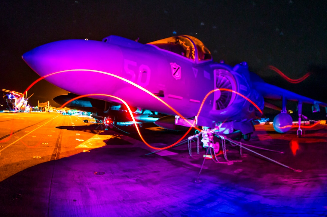 An aircraft sits on a flight deck at night as light from various machinery swirls nearby.