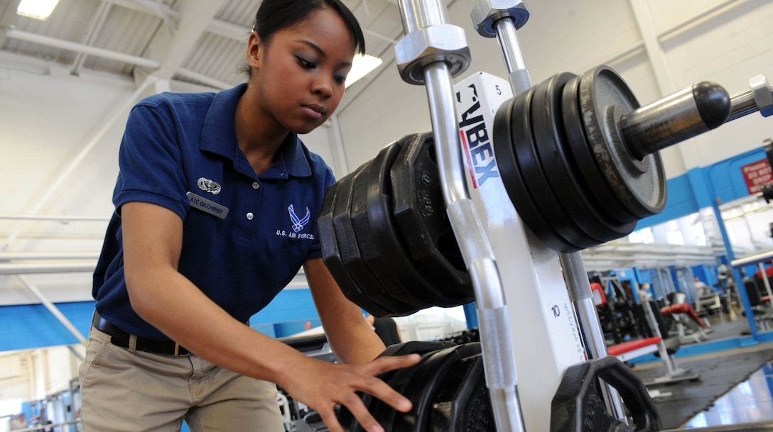 ELLSWORTH AIR FORCE BASE S.D.-- Airman 1st Class Elimae Gilchrist, 28th Force Support Squadron fitness specialist, puts away weights at the Bellamy Fitness Center, Feb. 11. The fitness center serves active-duty members, retirees, Department of Defense civilians and their families. (U.S. Air Force photo/Airman 1st Class Corey Hook)