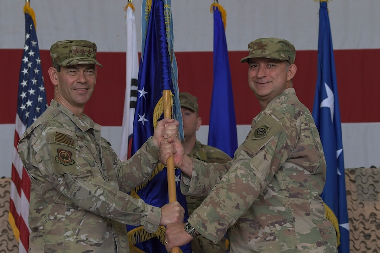 U.S. Air Force Lt. Gen. Kenneth Wilsbach, Seventh Air Force commander, presents the guidon to the 51st Fighter Wing's newest commander, Col. John Gonzales, during a change of command ceremony, June 18, 2019, at Osan Air Base, Republic of Korea. Gonzales, a prior 25th Fighter Squadron A-10C Thunderbolt II pilot, will again carry the Mustang tradition. Now, he leads the most forward deployed wing in the world, providing combat ready forces in support of the ROK. (U.S. Air Force photo by Staff Sgt. Greg Nash)