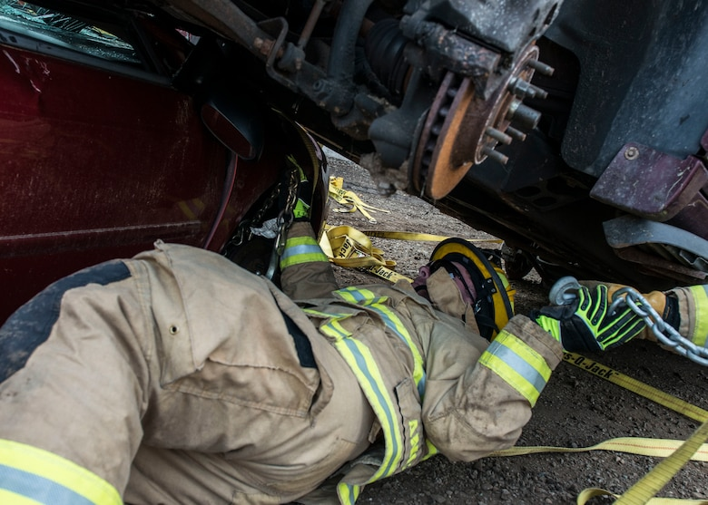 A firefighter assigned to the 103rd Civil Engineer Squadron, Connecticut Air National Guard attempts to remove a vehicle off of another vehicle as part of an auto accident scenario during a rescue strike team exercise, June 1, 2019 in East Granby, Conn. The firefighters trained with members of several local fire departments to ensure continuity in training across departments. (U.S. Air National Guard photo by Tech. Sgt. Tamara R. Dabney)