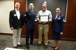 From left to right Mr. Kevin Spalding Area Chair with the North Carolina ESGR, U.S. Air Force Tech. Sgt. Stacey Wakefield of the 156th Aeromedical Evacuation Squadron, Mr. Chris Mendlik Wells Fargo Information Security Manager, and Master Sgt. Sara Evans with the 131st Bomb Wing pose for a photo after presenting Mr. Mendlik the ESGR Patriotic Employer Award at the Wells Fargo Charlotte Customer Information Center, NC, June 14, 2019. The Patriotic Employer Award is the first level that an employer can be nominated for, and reflects the efforts made to support citizen warriors through a wide-range of measures including flexible schedules, time off prior to and after deployment, caring for families, and granting leaves of absence if needed.