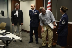 From left to right Mr. Kevin Spalding Area Chair with the North Carolina ESGR, U.S. Air Force Tech. Sgt. Stacey Wakefield of the 156th Aeromedical Evacuation Squadron, Mr. Chris Mendlik Wells Fargo Information Security Manager, and Master Sgt. Sara Evans with the 131st Bomb Wing laugh after Mr. Mendlik was surprised by a ceremony to present the ESGR Patriotic Employer Award at the Wells Fargo Charlotte Customer Information Center, NC, June 14, 2019. The Patriotic Employer Award is the first level that an employer can be nominated for, and reflects the efforts made to support citizen warriors through a wide-range of measures including flexible schedules, time off prior to and after deployment, caring for families, and granting leaves of absence if needed.