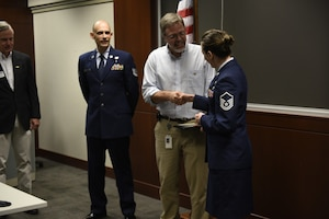 U.S. Air Force Master Sgt. Sara Evans a traditional guardsman with the 131st Bomb Wing in Missouri presents Mr. Chris Mendlik her civilian supervisor at Wells Fargo, with a challenge coin after she and Tech. Sgt. Stacey Wakefield of the North Carolina Air National Guard presented Mr. Mendlik with the ESGR Patriotic Employer Award at the Wells Fargo Charlotte Customer Information Center, NC, June 14, 2019. The Patriotic Employer Award is the first level that an employer can be nominated for, and reflects the efforts made to support citizen warriors through a wide-range of measures including flexible schedules, time off prior to and after deployment, caring for families, and granting leaves of absence if needed.
