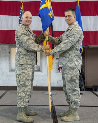 U.S. Air Force Col. Timothy Trimmell, 52nd Maintenance Group commander, left, gives the ceremonial guidon to U.S. Air Force Maj. Eric Burke, incoming 52nd Maintenance Squadron commander, right, during the 52nd MXS change of command ceremony at Spangdahlem Air Base, Germany, June 17, 2019. (U.S. Air Force photo by Airman 1st Class Branden Rae)