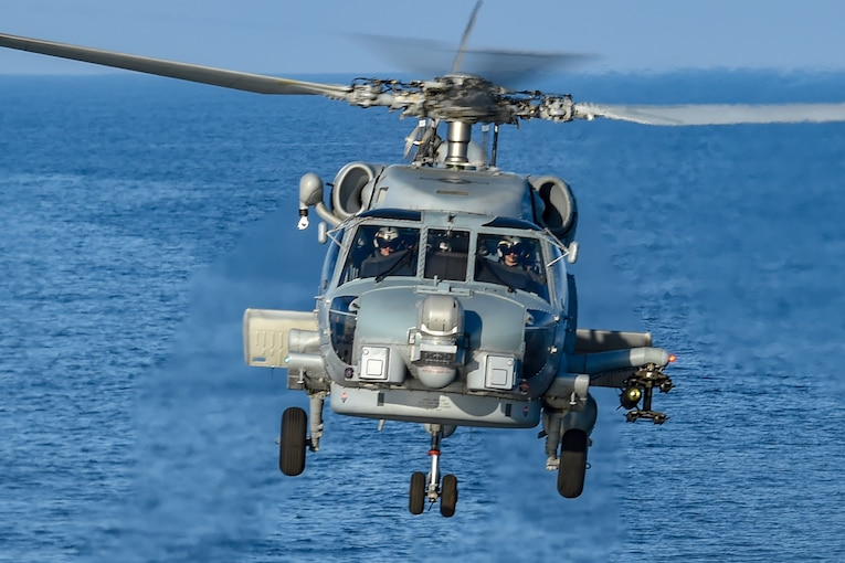 A helicopter flies above water as it heads toward the camera.
