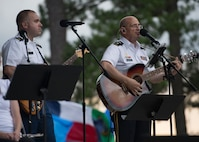 """U.S Army Maj. Gen. Paul M. Benenati, U.S. Army Training and Doctrine Command deputy chief of staff, plays guitar during the """"Music Under the Stars"""" concert series at Joint Base Langley-Eustis, Virginia, June 13, 2019."""