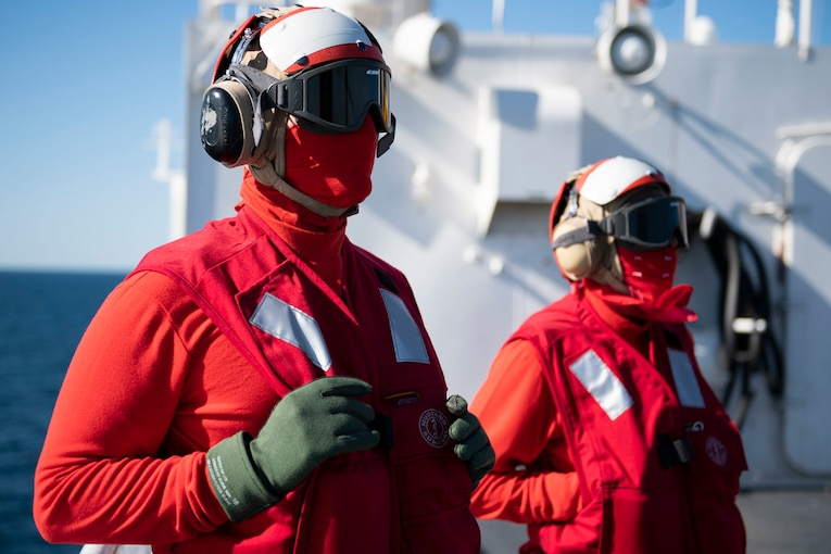 Sailors wearing goggles, earphones, red vests and scarves stand on a ship's flight deck.