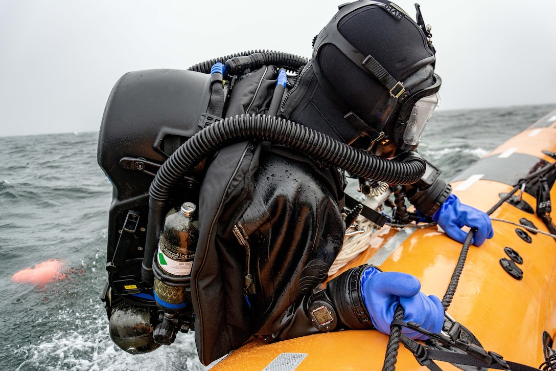A half-submerged diver in a wetsuit carrying an oxygen tank holds on to a rope alongside a yellow raft.