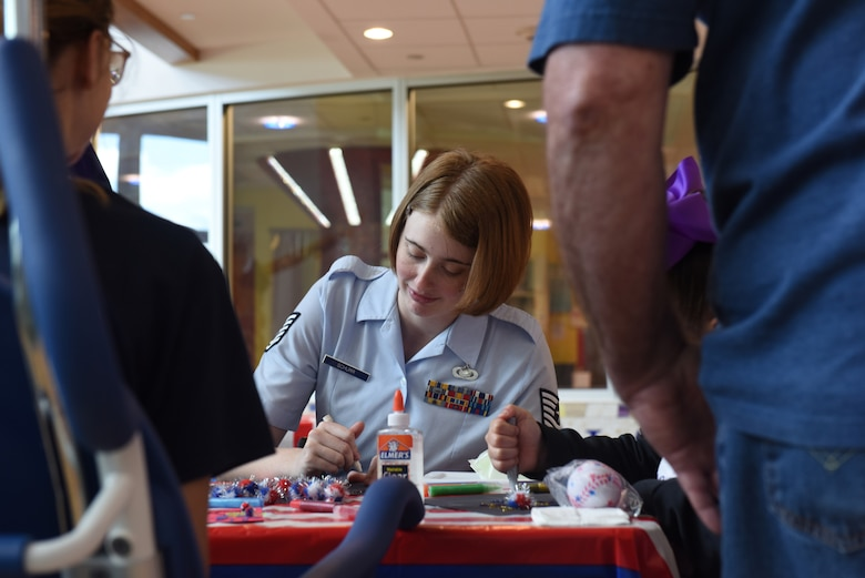 Tech. Sgt. Marjorie A. Schurr, NCO in charge of community engagement with the 911th Airlift Wing, makes glitter glue fireworks with patients and their families at Children's Hospital of Pittsburgh, June 14, 2019.