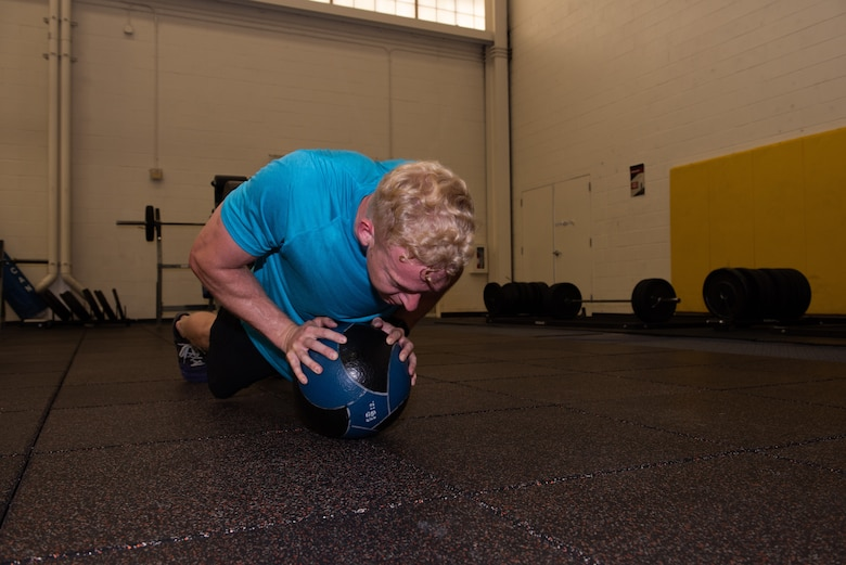 U.S. Air Force Capt. Christopher Williston, a 21st Airlift Squadron C-17 Globemaster III pilot from Baton Rouge, Louisiana, performs push-ups on an 18-pound medicine ball during a workout June 13, 2019, at Travis Air Force Base, California. Williston is training to compete in the Alpha Warrior Western Regional Competition June 21 at Hill AFB, Utah. (U.S. Air Force photo by Tech. Sgt. James Hodgman)