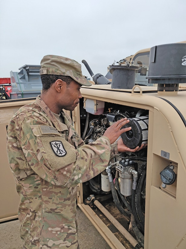 U.S. Army Sgt. Brian Mitchell, a member of DLA's Disposition Services Unit 1, out of Joint Base Lewis-McChord, examines the engine on material handling equipment his team will use at its mobile site in Kosovo in June.