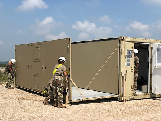 Expeditionary disposal team members prepare a command and control shelter at Camp Bondsteel in Kosovo. The military-civilian team will spend two weeks in the Slavic nation helping U.S. Army units discard a wide variety of accumulated used materiel.