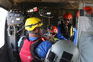 Members of the Mississippi Task Force Urban Search and Rescue team are harnessed to a hoist before being lowered from a helicopter during rooftop rescue training May 31, 2019 at Camp McCain, Mississippi. The joint training between the civilian task force and the military was part of Ardent Sentry 2019, an exercise training Mississippians to help Mississippians in times of crisis and be ready to assist in recovery efforts. (U.S. Army National Guard photo by PFC Austin Eldridge/RELEASED)